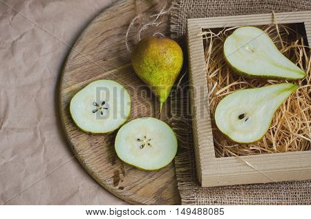 Ripe and juicy pears on background of packing paper canvas burlap and wooden board toned and faded