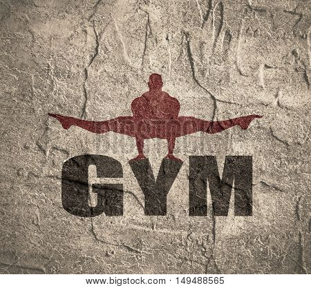 Muscular man posing on gym word. Concrete texture. Bodybuilding relative image