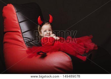 photo of funny little devil on dark background