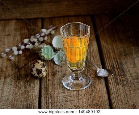 quail eggs in a glass, salt and twigs of willow on a wooden background