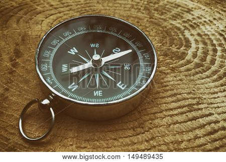 Compass on a wooden surface close-up stained glass styling selective focus