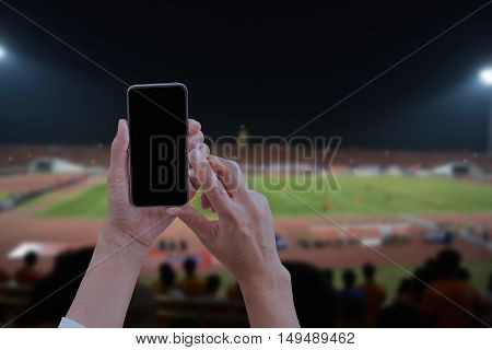 Hand holding mobile smart phone with black screen blur image of a football field as background.