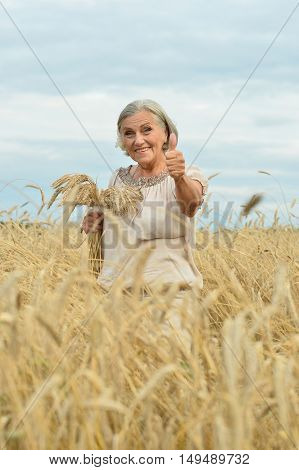 Portrait of  senior woman in summer field with thumb up