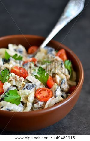 Holiday salad with mushrooms tomatoes and sauce on a black background.
