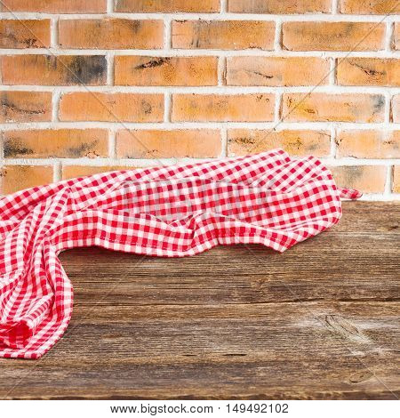 wooden table with with cloth napkin red brick kitchen wall