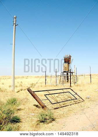 The ruins of the power line and the gate in the steppe near Mayskiy Uzbekistan