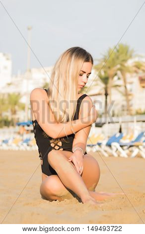 Sexy woman sit on the sandy beach in black swimsuit