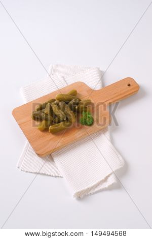 pile of pickled cucumbers on wooden cutting board