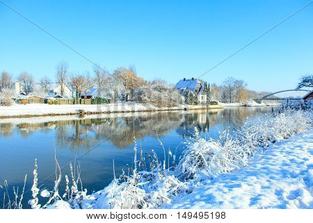 The picturesque landscape of the river, snowy shore on a sunny day in early winter
