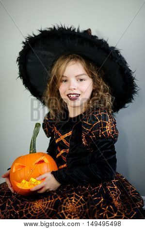 Beautiful girl of younger school age in an image of the evil witch. Girl has dressed up by Halloween. In hands at her orange pumpkin - Jack o lantern. Children like Halloween.