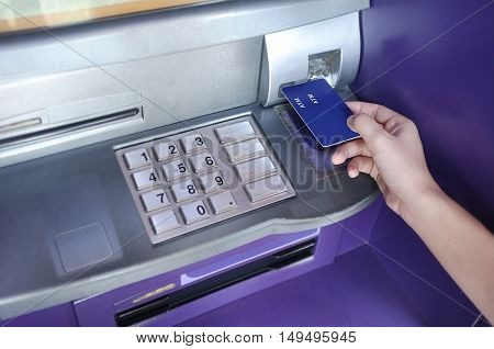 Close-up of hand entering card on ATM/bank machine
