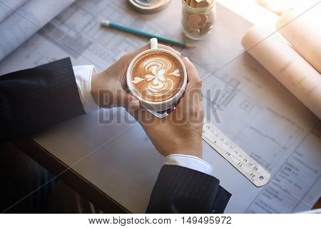 Architects drinking Latte art coffee while Discussing Plan in office.