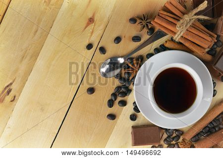 A cup of coffee chocolate and star anise. coffee beans cinnamon bunch. Snack. Sweet Tooth. Break. Gourmet. Enjoyment. Top view. The fragrance of the holiday. Christmas. Home comfort. Memories. Modern life. Traditions.