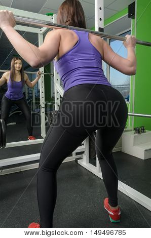 fitness concept - sporty woman exercising with barbell in gym