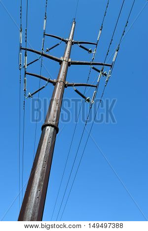 Utility tower and power lines against a clear blue sky