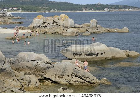 LA TOJA, SPAIN - AUGUST 8, 2016: People having a bath in the sea of a beach in the Island of La Toja in the province of Pontevedra Galicia Spain.