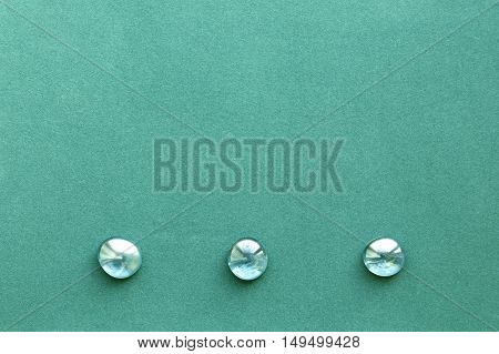 Turquoise rough paper background with three smooth glass pebbles in a bottom