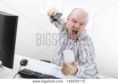 Very angry businessman aiming gun on mobile phone at computer desk in office