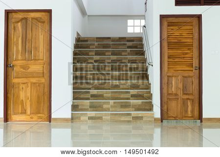 white empty room interior with wooden door and staircase