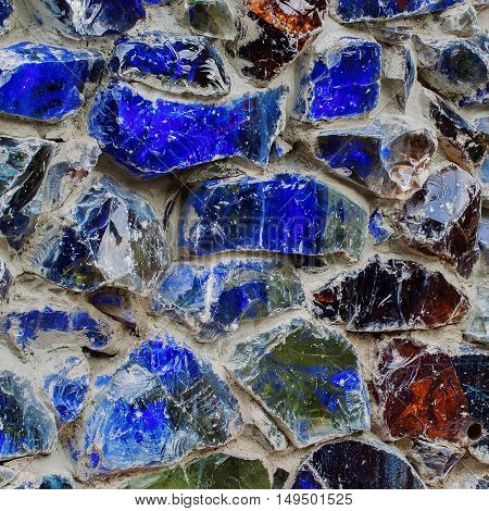 Part of the rough walls close up decorated with colored blue stones, texture background. Square