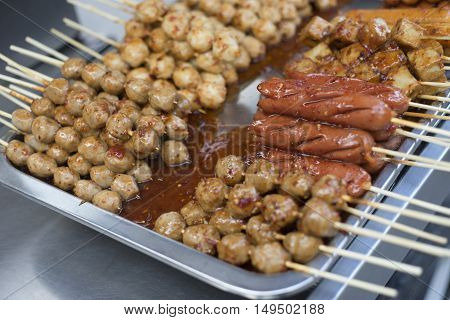 close up many type of grilled meat ball and sausage with sauce put on metal plate,thai street food