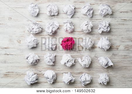 Set of crumpled white paper balls with one pink ball.