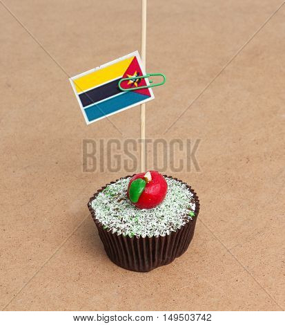 Flag of mozambique on cupcake on wood background