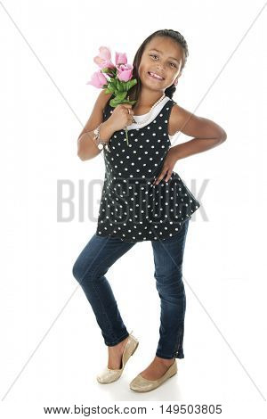 A pretty elementary girl looking sassy as she stands with a bouquet of pink roses.  On a white background.