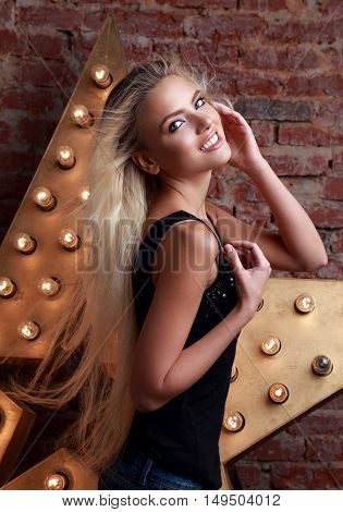 Young Smiling Woman Posing With Long Blond Hair On Star And Brick Wall Background