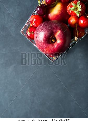Fresh fruit and berries - cherries, peaches and strawberries - in a supermarket cart on black background. Copy space. Vertical image