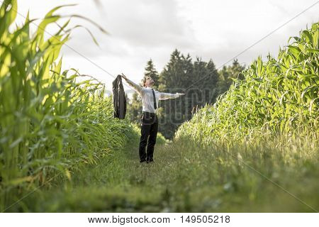 Person in necktie holding blazer while standing in between rows of corn in field with bright yellow sunlight.