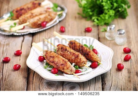 Homemade meat kebabs skewers with dogberry and onion salad on wooden background.