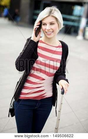 Smiling young woman talking on smart phone outside railroad station
