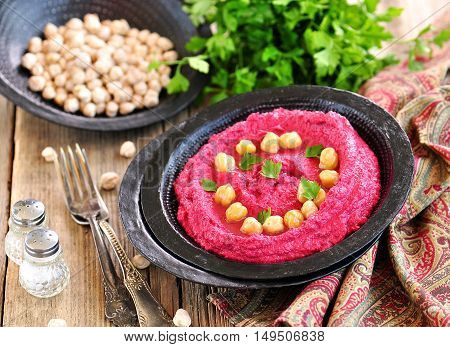 Beetroot hummus with chickpeas and olive oil on old wooden background.
