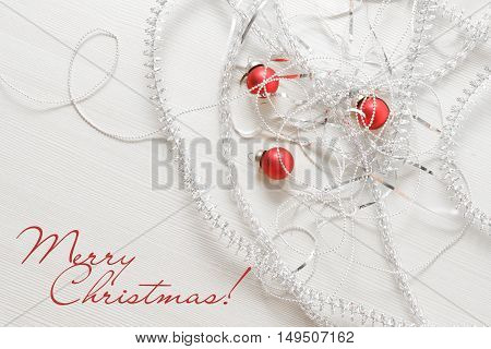 New year and Christmas greeting card template made of different silver tinsels and beads red balls against wooden background with copy space top view