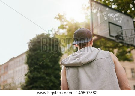 Rear view shot of a streetball player standing on outdoor basketball court on a summer day.
