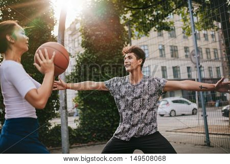 Two young man and woman playing streetball against each other. Teenage friends playing a game of basketball on an outdoor court.