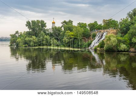 Summer landscape with artificial waterfall and Orthodox church on a Dnepr river island in center of Dnepr city Ukraine