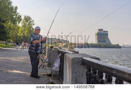 DNEPR, UKRAINE - AUGUST 21, 2016: Senior fisherman fishing on a Dnepr river embankment at summer weekend in Dnepr Ukraine at August 21 2016