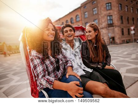 Three young people having fun on tricycle in the city. Young man and women riding on tricycle on road and smiling.