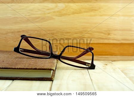Glasses and brown color notebook on wooden table. Education concept.