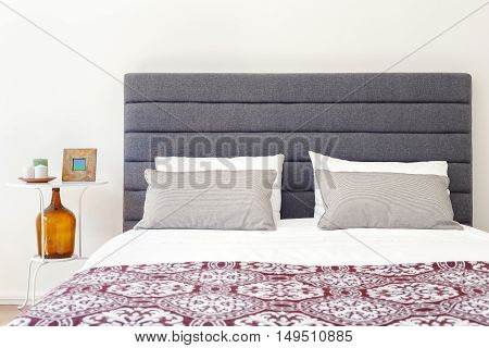 Relaxing soft bed and nightstand on a bright room