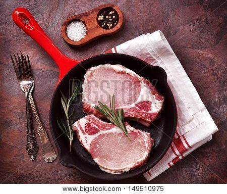 Raw pork chop in a frying pan with rosemary, pepper and salt.
