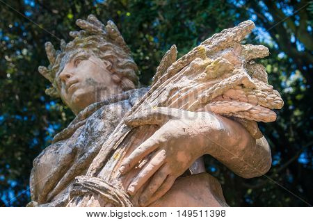 Ceramic statue of the summer with a woman holding a bundle of wheat public gardens in Caltagirone Sicily