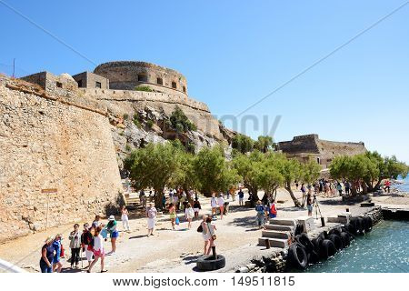 SPINALONGA GREECE - MAY 14: The tourists are on Spinalonga island on May 14 2014 in Spinalonga Greece. Up to 16 mln tourists is expected to visit Greece in year 2014.