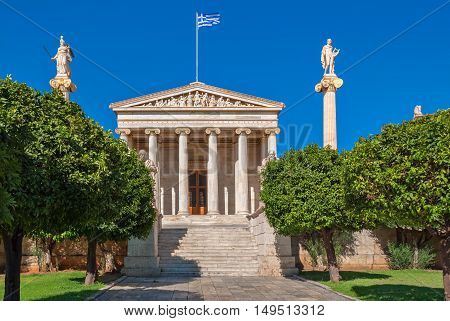 The facade of Athens Academy of Sciences with the main staircase and the statues of Apollo and Athena on high columns.