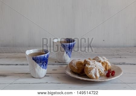 eclairs on a white plate blue and white hand-made ceramic tableware cookies on a ceramic plate a pair of clay cup on a white background