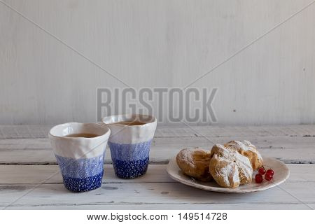 eclairs on a white plate, blue and white hand-made ceramic tableware, cookies on a ceramic plate,  a pair of clay cup on a white background, tea with sweet dessert.