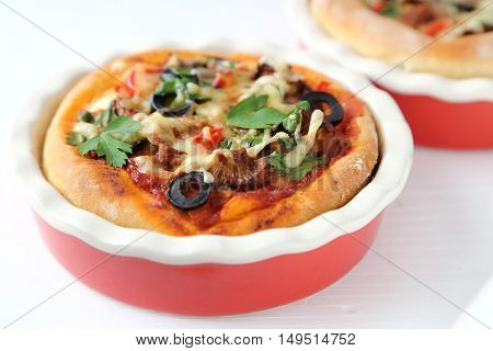 Casserole with mushrooms olives peppers and cheese on the dough for pizza.