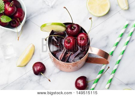 Cold cherry Moscow Mules cocktail with ginger beer, vodka, lime Marble background Copy space Top view